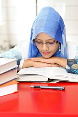 A young muslim woman reading a book