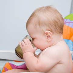 Lovely baby sitting in chair and drinking from baby cup