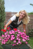 Happy woman with flowers in her garden
