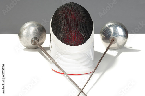 fencers sword and mask on a white background