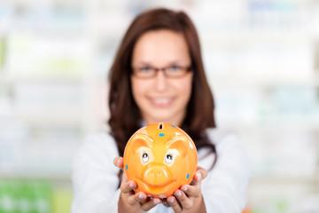 lächelnde apothekerin zeigt sparschwein