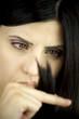 Beautiful female model looks at her split ends hair closeup