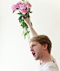 Young man fighting for his love with flowers