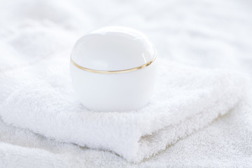 cosmetic containers lying on white towel