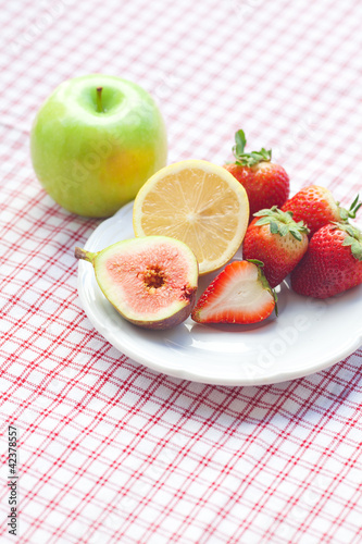 apple,lemon, fig and strawberries on a plate