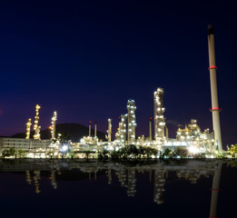 Reflection of petrochemical industry on sunset dark blue sky.