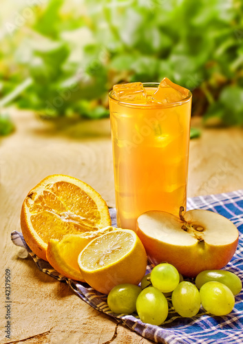 Juice, orange, apple, grape and lemon on the table, outdoor