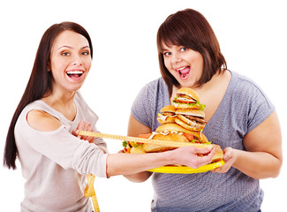 Woman holding fast food and measuring tape.