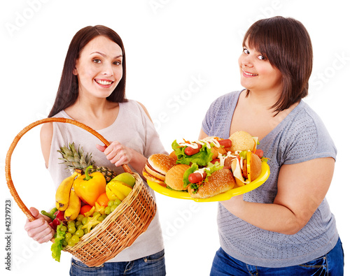 Women choosing between fruit and hamburger.