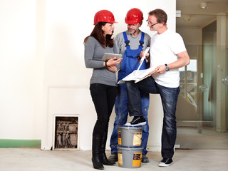 Architect, worker and customer making plans in building lot