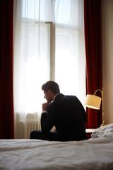 junger Mann im Anzug sitzt auf Hotelbett