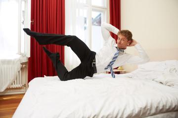 Junger Mann springt in Hotelbett