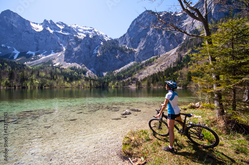 Yaung woman riding a bike beside Alpine lake