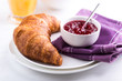Croissant and raspberry jam in a small bowl
