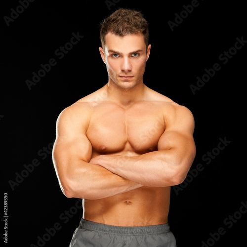 Handsome man with arms crossed looking his left on black