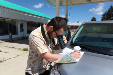 Man Studies Roadmap with Binoculars