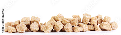 Lump brown cane sugar cubes isolated on white