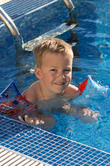 A little boy learns to swim in the pool