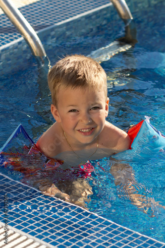 A little boy swims in the pool