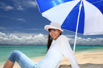 ビーチパラソルの下で寛ぐ笑顔の女性
