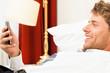 Geschäftsmann liest SMS im Hotelbett