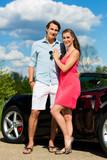 Junges Paar mit Cabrio im Sommer auf einem Ausflug