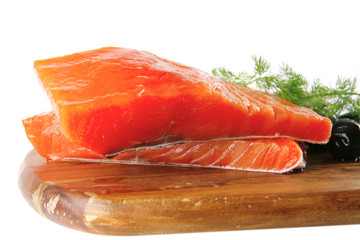 smoked salmon on wooden plate with white cheese