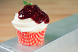 Frosted white cupcake with raspberry sauce