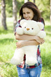 Beautiful teen girl with Teddy bear in the park at green grass.
