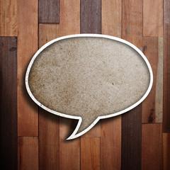 paper speech bubble on wood background.