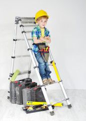 Little boy handyman with helmet and tool belt on stepladder. Equ