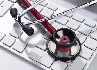 Rotes Stethoskop auf tastatur close-up