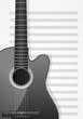 realistic acoustic guitar with musical sheet as background