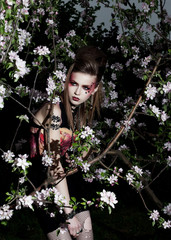 Beautiful woman among spring blossom. Flowers of apple tree