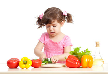 Little girl cutting vegetable for salad. Concept of healthy food