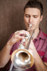 Handsome man playing on a silver trumpet