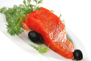 fresh smoked salmon on white plate with olives