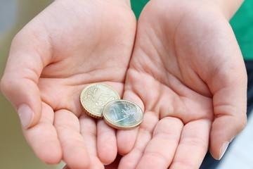 mani con monete da 1,50 euro