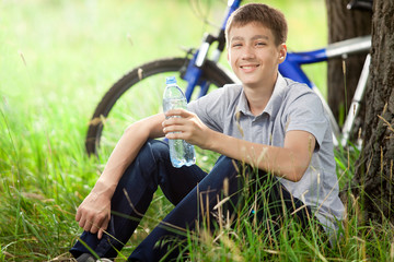 The cyclist in the park drinking clean water