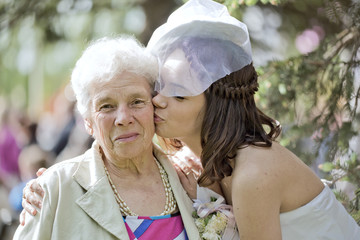 The young girl kisses the elderly woman