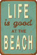 "Vintage style tin sign with text ""Life is good at the Beach""."