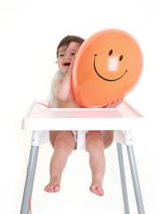 Baby peeping round happy balloon