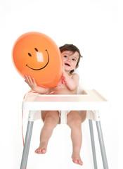 Baby holding happy balloon