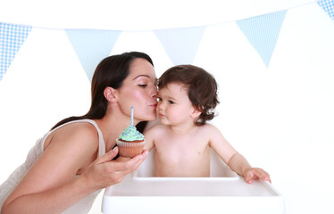 Mother giving kiss on cheek to baby - Happy birthday!
