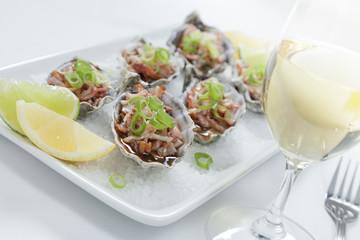 Oven baked oysters kilpatrick on a bed of rocksalt