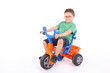 young boy riding his tricycle