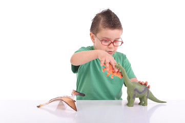 young kid playing with dinosaurs