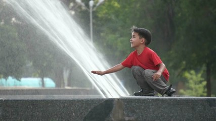 Boy touching a fountain on a summer day.