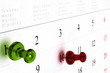 weekly calendar with green and red thumbtack s