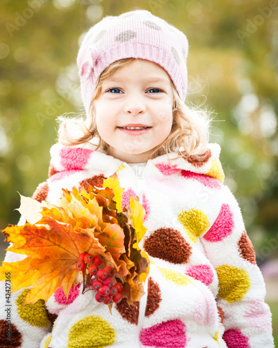 Child with bunch of maple leaves